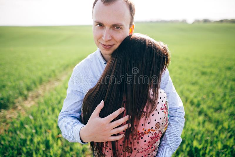 Mooi jong paar die zacht in zonneschijn op de lente groen gebied koesteren Gelukkige familie die in groene weide met vers gras om royalty-vrije stock afbeeldingen