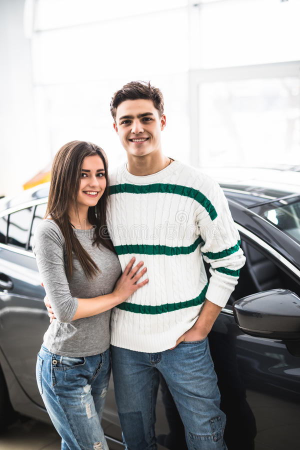 Mooi jong paar die zich bij het autohandel drijven bevinden en hun besluit nemen royalty-vrije stock foto