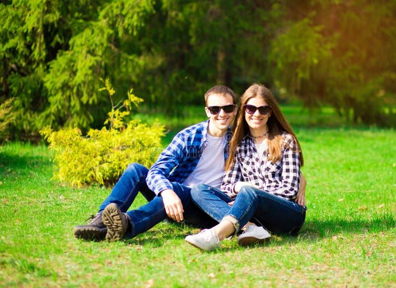 Mooi jong paar die in zonnebril met aardachtergrond omhelzen stock fotografie