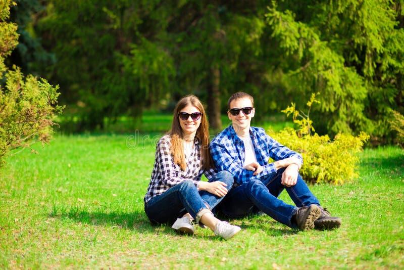 Mooi jong paar die in zonnebril met aardachtergrond omhelzen stock foto's