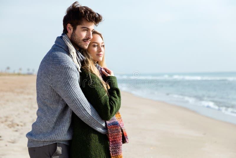 Mooi jong paar in liefde in de koude winter op het strand stock foto's