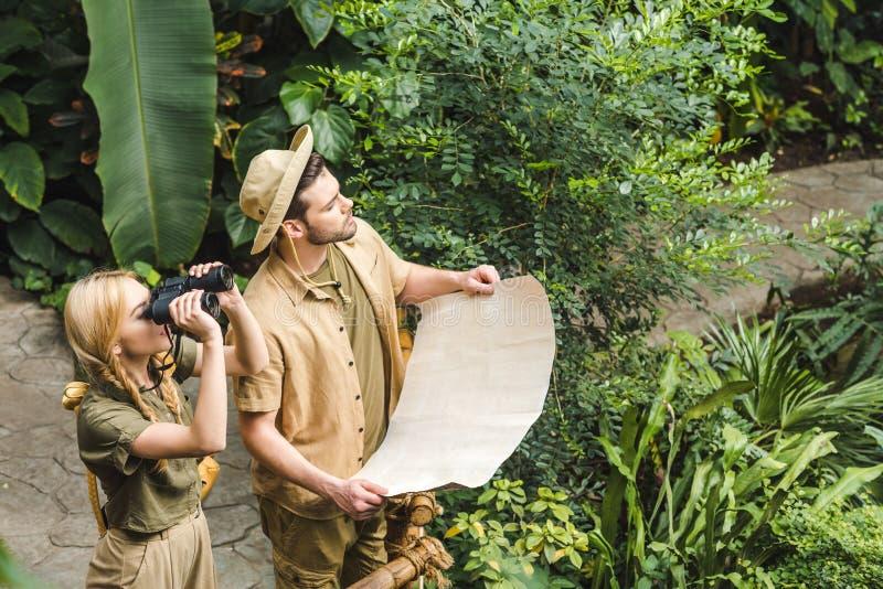 mooi jong paar in safarikostuums met kaart en verrekijkers royalty-vrije stock foto