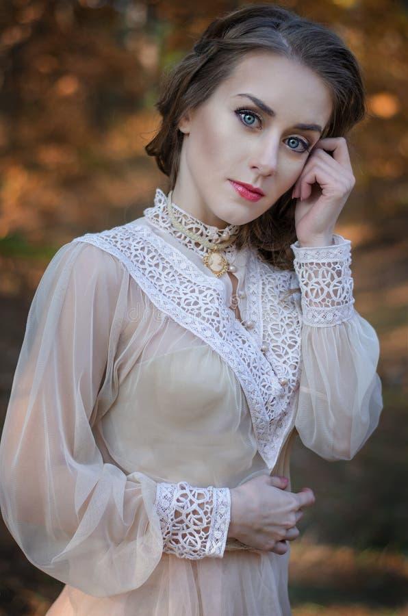 Mooi jong roodharig meisje met blauwe ogen in een zachte kleding die zich in een bos in de achtergrond de herfstbomen bevinden royalty-vrije stock foto