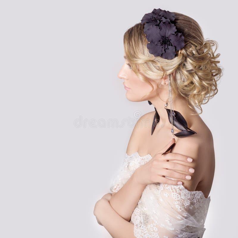 mooi jong sexy elegant zoet meisje in het beeld van een bruid met haar en bloemen in haar haar, gevoelige huwelijksmake-up royalty-vrije stock afbeelding