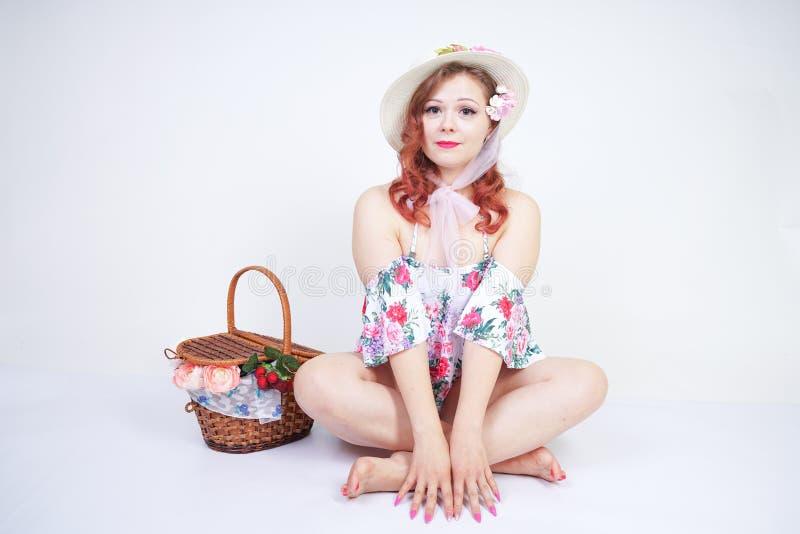 Mooi jong speld omhoog Kaukasisch meisje in romantische modieuze strohoed, uitstekend zwempak met bloemen en retro rieten mand po stock afbeeldingen