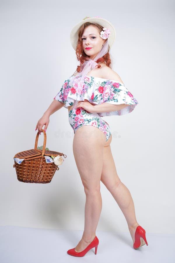 Mooi jong speld omhoog Kaukasisch meisje in romantische modieuze strohoed, uitstekend zwempak met bloemen en retro rieten mand po stock afbeelding