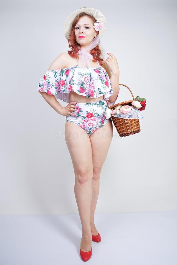 Mooi jong speld omhoog Kaukasisch meisje in romantische modieuze strohoed, uitstekend zwempak met bloemen en retro rieten mand po royalty-vrije stock afbeelding