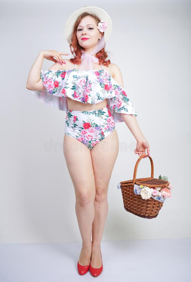 Mooi jong speld omhoog Kaukasisch meisje in romantische modieuze strohoed, uitstekend zwempak met bloemen en retro rieten mand po royalty-vrije stock foto