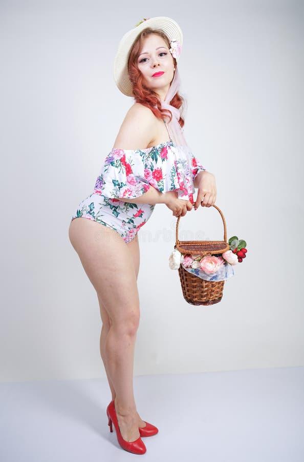 Mooi jong speld omhoog Kaukasisch meisje in romantische modieuze strohoed, uitstekend zwempak met bloemen en retro rieten mand po royalty-vrije stock fotografie