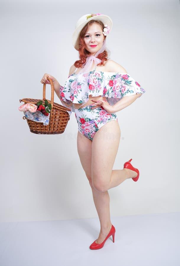 Mooi jong speld omhoog Kaukasisch meisje in romantische modieuze strohoed, uitstekend zwempak met bloemen en retro rieten mand po royalty-vrije stock foto's