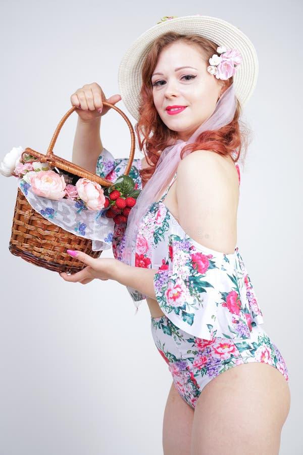 Mooi jong speld omhoog Kaukasisch meisje in romantische modieuze strohoed, uitstekend zwempak met bloemen en retro rieten mand po stock foto