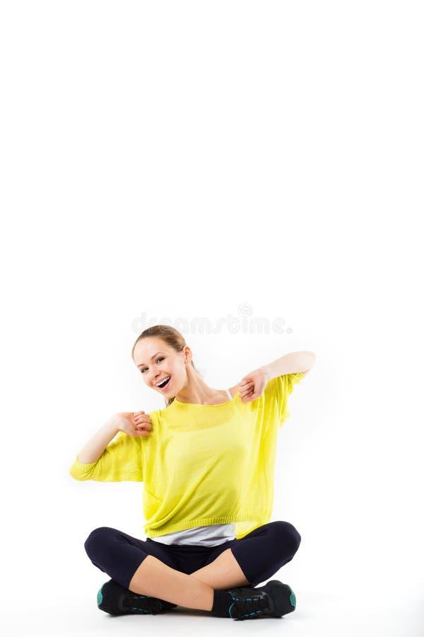 Mooi jong sportief meisje die en een onderbreking van haar training zitten nemen stock foto