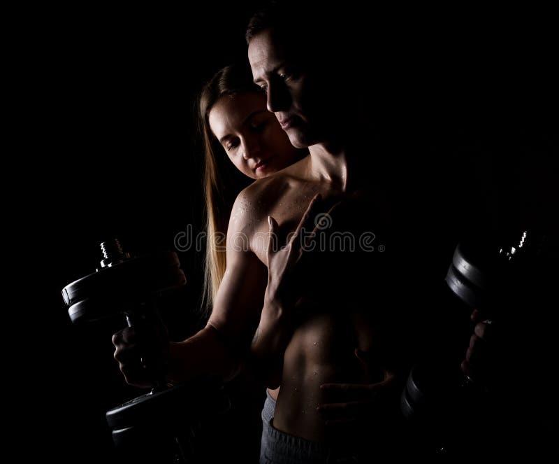 Mooi jong sportief sexy paar die spier op een donkere achtergrond tonen royalty-vrije stock foto's