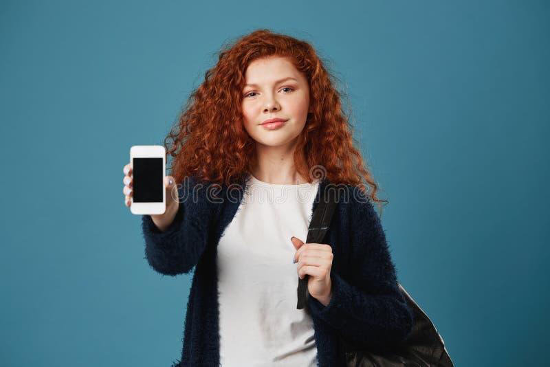 Mooi jong tiener roodharig meisje met sproeten die celtelefoon tonen in camera, houdend rugzak met hand, die hebben royalty-vrije stock foto