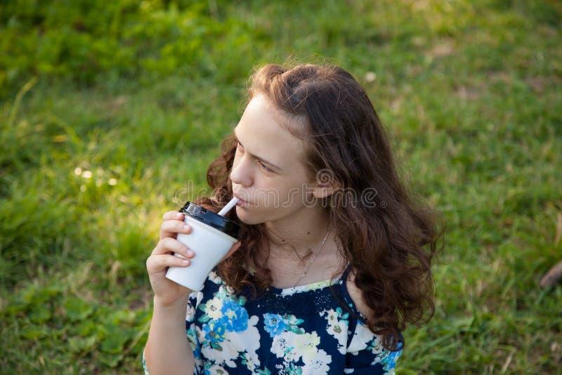 Mooi jong tienermeisje die een cocktail drinken bij een picknick in het hout in de zomer royalty-vrije stock afbeelding