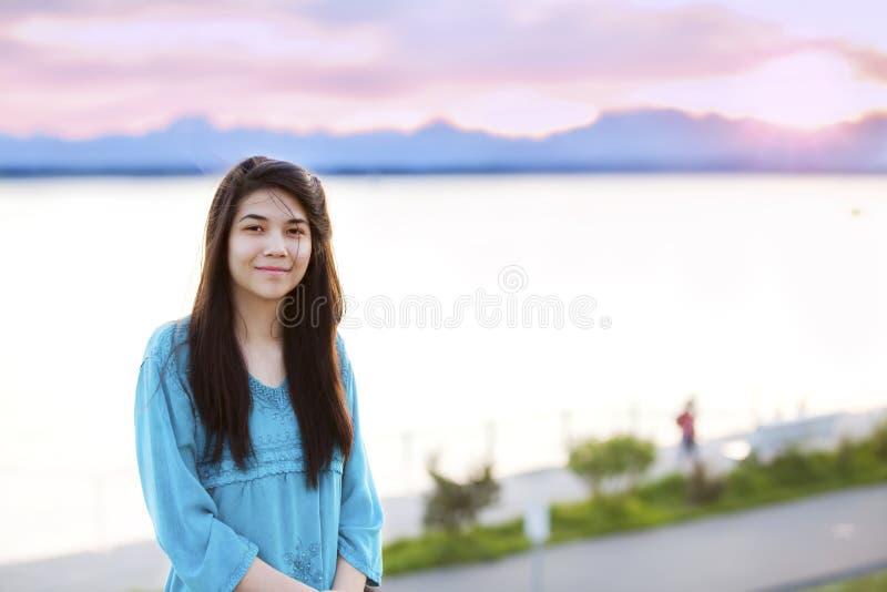 Mooi jong tienermeisje die in openlucht van door meer bij zonsondergang genieten stock foto's
