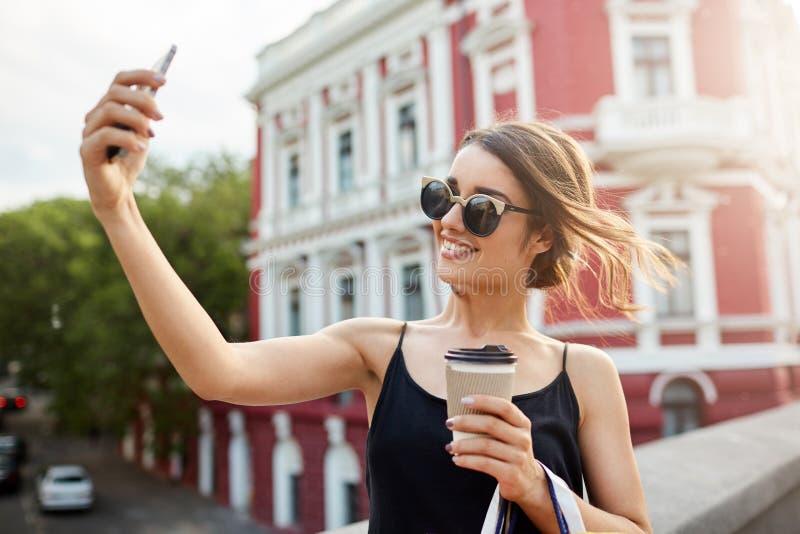 Mooi jong vrolijk donker-haired Spaans meisje in zonnebril een zwarte kleding die met tanden glimlachen, die selphie binnen nemen stock foto's