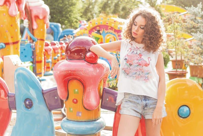 Mooi jong vrolijk meisje met krullend haar in denimborrels en witte T-shirt bij een pretpark bij zonsondergang heldere zon royalty-vrije stock fotografie