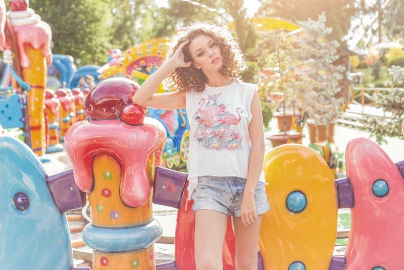 Mooi jong vrolijk meisje met krullend haar in denimborrels en witte T-shirt bij een pretpark bij zonsondergang heldere zon royalty-vrije stock afbeeldingen
