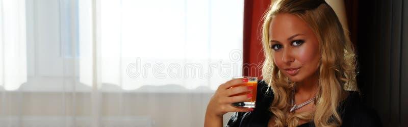 Mooi jong vrouw het drinken sap binnen royalty-vrije stock foto's