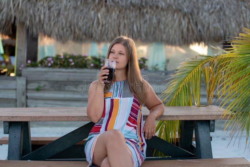 Mooi jong vrouw het drinken sap op strand stock afbeeldingen