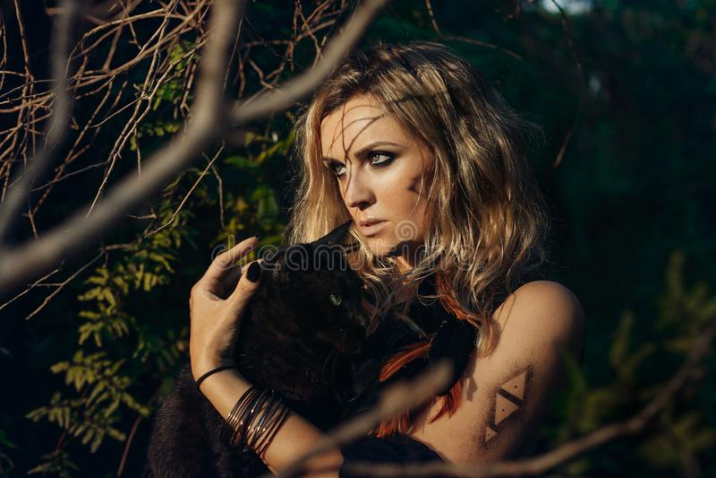Mooi jong vrouwen modelportret met zwarte kat in bosw stock afbeelding