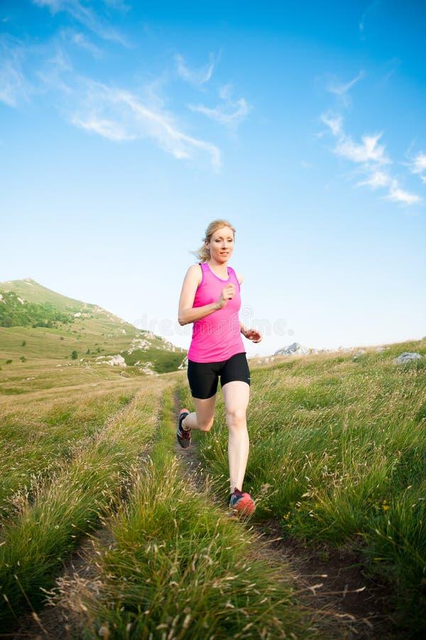 Mooi jong vrouwen runns dwarsland op een mountian weg bij stock afbeelding