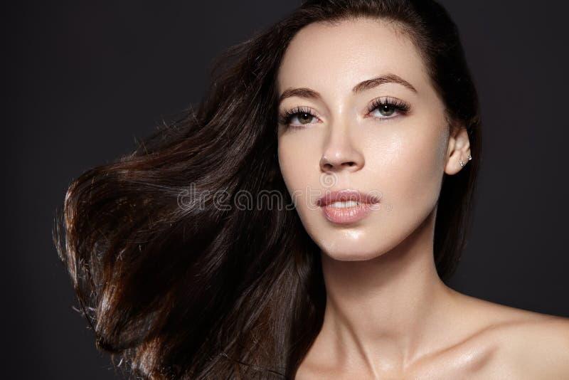 Mooi jong vrouwenmodel met vliegend bruin kleurenhaar Maak omhoog, krullend kapsel Haircare, samenstelling stock afbeelding