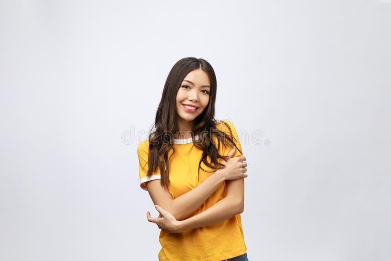 Mooi jong vrouwenportret Het glimlachen Aziatisch levensstijlconcept met gekruiste wapens Geïsoleerd op grijze achtergrond royalty-vrije stock foto