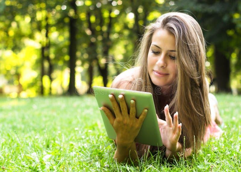 Mooi jong wijfje die digitale tabletpc met behulp van stock foto's