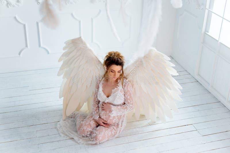 Mooi jong zwanger meisje met grote engelenvleugels royalty-vrije stock foto