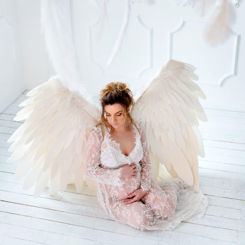 Mooi jong zwanger meisje met grote engelenvleugels stock foto's