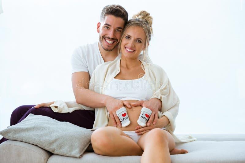 Mooi jong zwanger paar die camera bekijken terwijl thuis het houden van pari van sokken op buik van zijn zwangere vrouw stock foto's