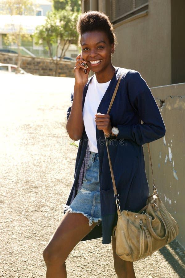 Mooi jong zwarte die in openlucht cellphone gebruiken royalty-vrije stock afbeelding