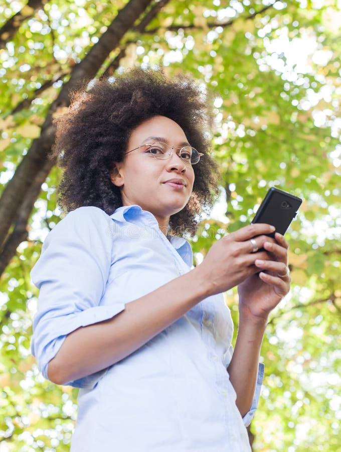 Mooi Jong Zwarte die Telefoon in Aard met behulp van royalty-vrije stock fotografie