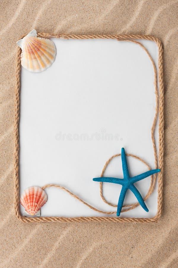 Mooi kader van kabel, sterren en zeeschelpen met een witte achtergrond op het zand, met plaats voor uw beeld, tekst royalty-vrije stock afbeelding