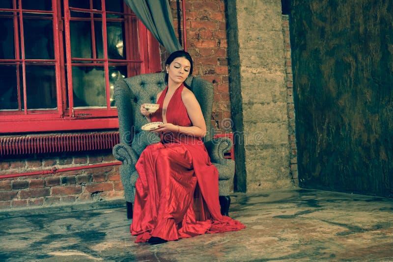 Mooi Kaukasisch meisje in een rode lange kleding op de achtergrond van een reusachtig nachtvenster met een grijs gordijn royalty-vrije stock afbeelding