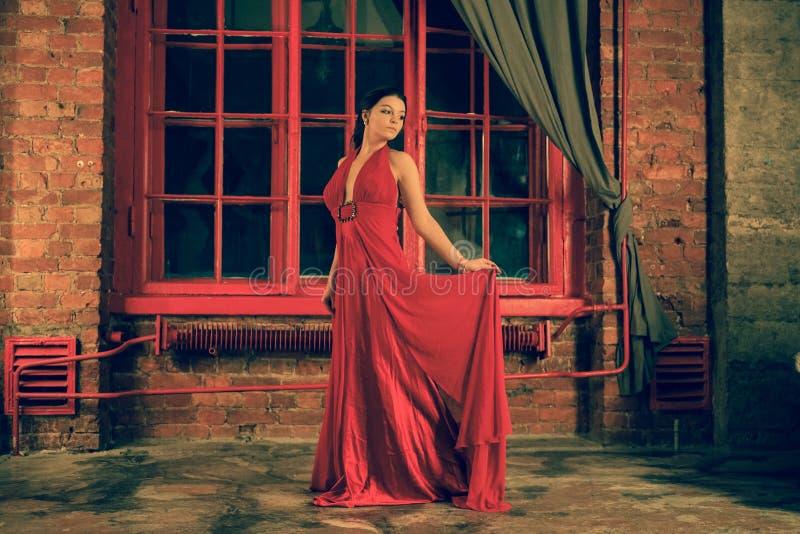 Mooi Kaukasisch meisje in een rode lange kleding op de achtergrond van een reusachtig nachtvenster met een grijs gordijn royalty-vrije stock afbeeldingen