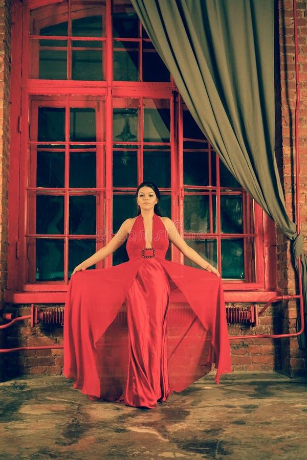 Mooi Kaukasisch meisje in een rode lange kleding op de achtergrond van een reusachtig nachtvenster met een grijs gordijn stock afbeelding