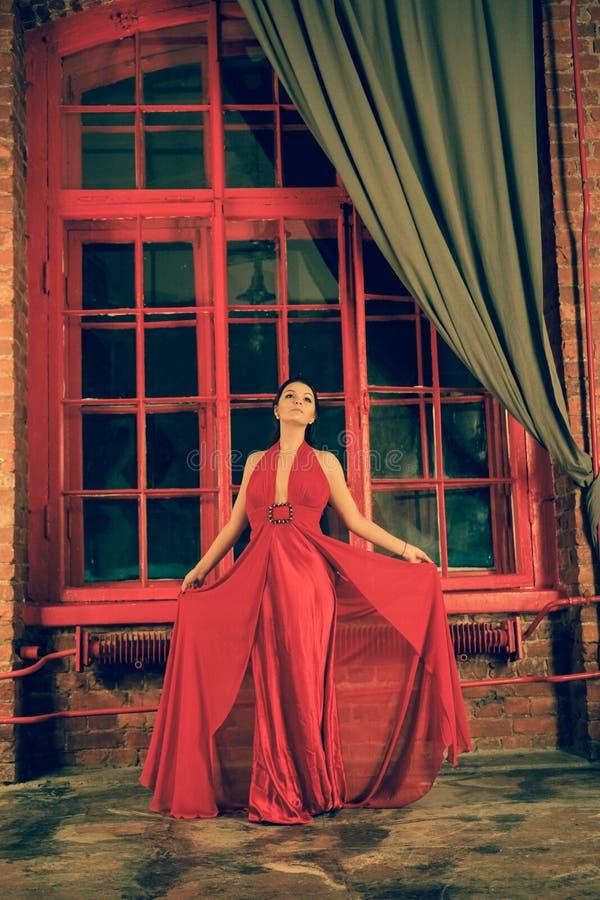 Mooi Kaukasisch meisje in een rode lange kleding op de achtergrond van een reusachtig nachtvenster met een grijs gordijn royalty-vrije stock foto