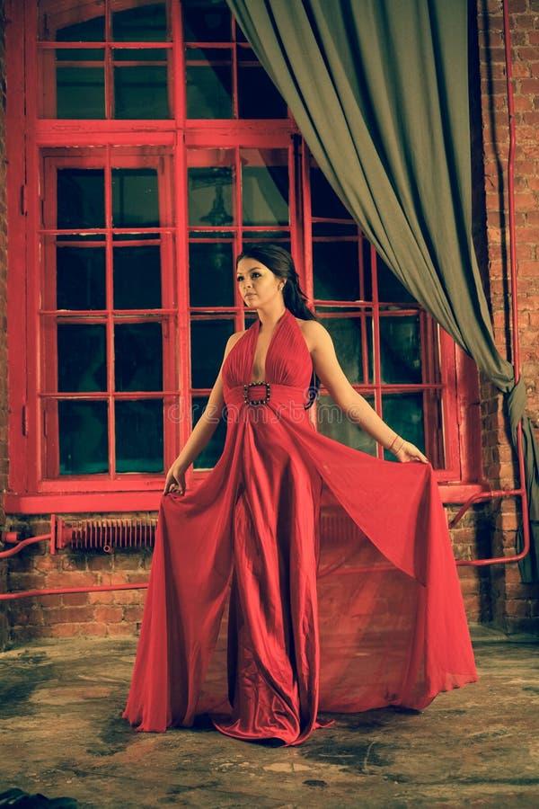 Mooi Kaukasisch meisje in een rode lange kleding op de achtergrond van een reusachtig nachtvenster met een grijs gordijn royalty-vrije stock foto's
