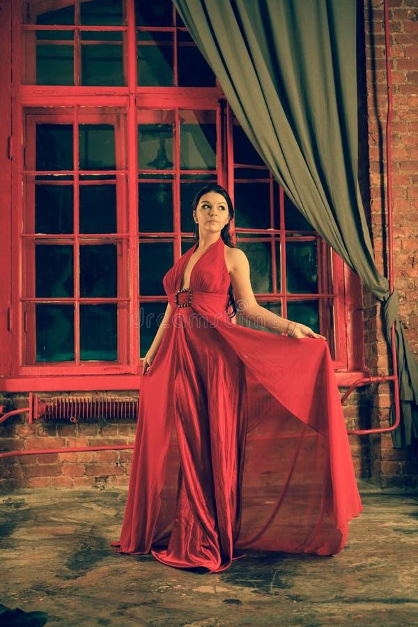 Mooi Kaukasisch meisje in een rode lange kleding op de achtergrond van een reusachtig nachtvenster met een grijs gordijn royalty-vrije stock fotografie