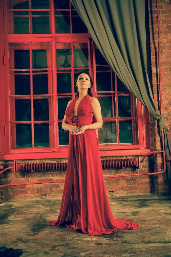Mooi Kaukasisch meisje in een rode lange kleding op de achtergrond van een reusachtig nachtvenster met een grijs gordijn stock afbeeldingen