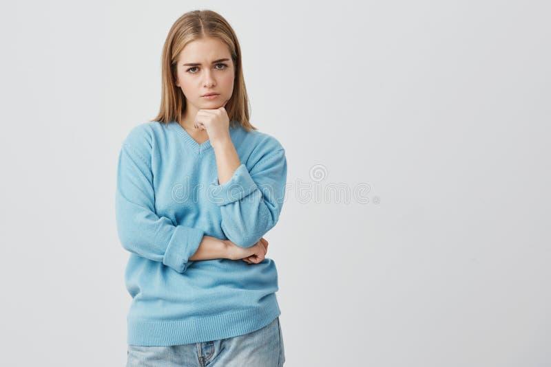 Mooi Kaukasisch ontevreden wijfje met recht eerlijk haar die vrijetijdskleding dragen die camera met woede bekijken stock fotografie