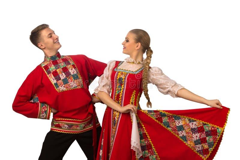 Mooi Kaukasisch paar die in Russische volksdiekostuums dansen op wit worden geïsoleerd royalty-vrije stock foto
