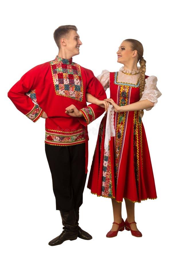 Mooi Kaukasisch paar die in Russische volksdiekostuums dansen op wit worden geïsoleerd stock fotografie