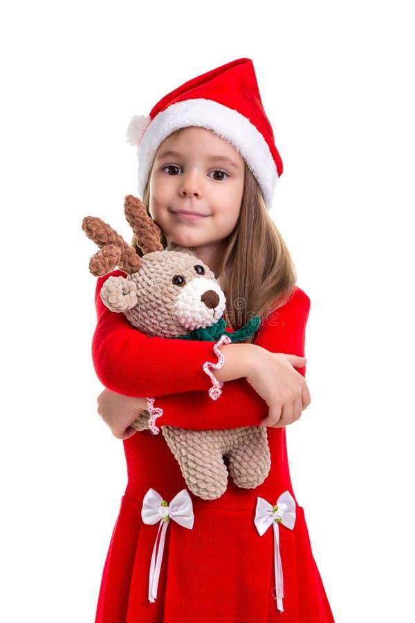 Mooi Kerstmismeisje die het herten zachte stuk speelgoed koesteren, die een santahoed dragen over een witte achtergrond wordt geï stock afbeelding