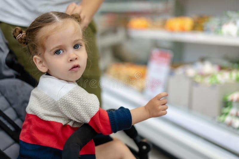Mooi kiest weinig Kaukasisch meisje producten in de supermarkt Close-upportret van een jonge koper stock fotografie