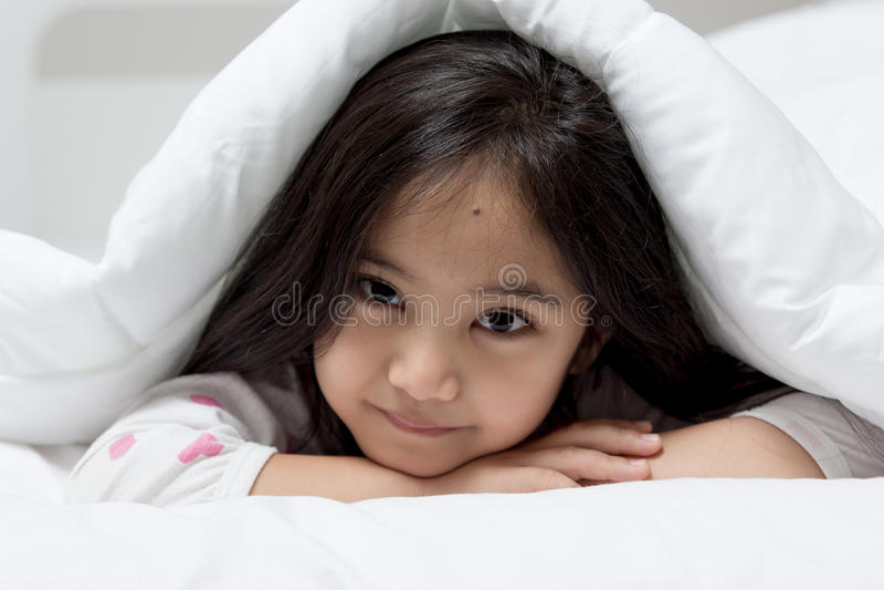 Mooi kind die op het bed bepalen stock foto's