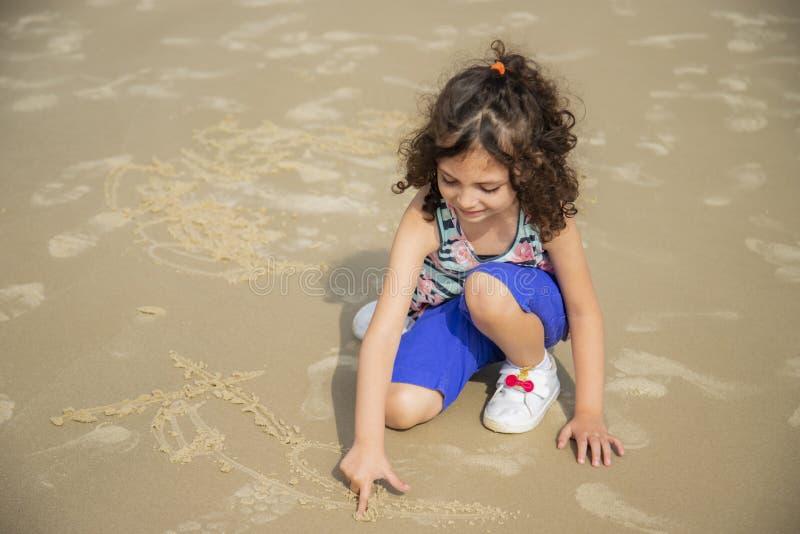 Mooi kind die op strandzand schrijven royalty-vrije stock foto